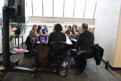 A photo of a seminar table surrounded by people with Kelly Fritsch sitting in at the head of the table.